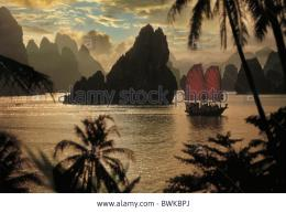Stock PhotoJunk in front of limestone formation at sunset, Halong 364