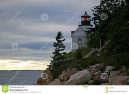 Small white lighthouse on rocky promontory cliff with trees at dusk 791