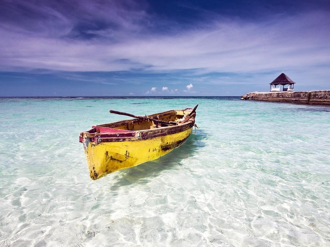 Lonely boat floating on crystal clear Caribbean sea wallpaper 1645