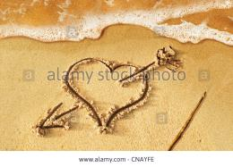 heart with arrow as love sign drawn on the beach shore with some water 875