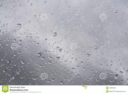 Waterdrops on glass surface against gray sky clouds 1160