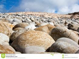 Round rocks on the beach with blue sky and clouds in the background 888