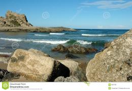 Large rocks on the beach with a rocky headland 994