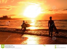 Kids with surfboards silhouetted against sunset over beach 1419