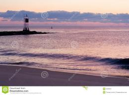 Scenic view of sunset over sea and beach with silhouetted mole and 814