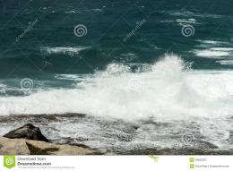 Waves breaking over rocks with spray going up in the air 1276