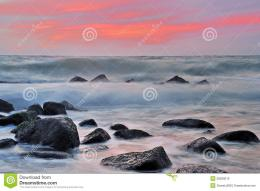 Waves breaking over rocks with colorful sunset background, Baltic sea 1021