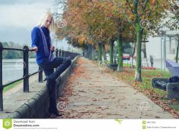 Beautiful young woman standing beside river on rainy autumn day 350