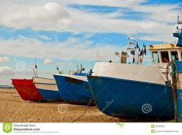The red and blue fishing boats on the seashore with the blue sky in 1229