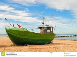 The green fishing boat on the seashore with the blue sky in the 624