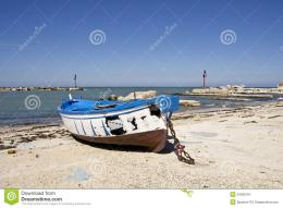 Free Stock Photography: Small fishing blue burnt boat on the seashore 1730