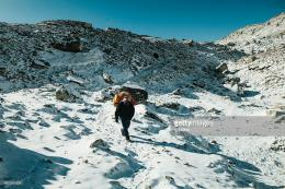 Nepalese porter walks through fresh snow beside the Khumbu Glacier 655