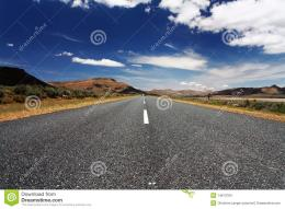 Long, lonely road in front of blue sky and mountains 319