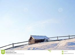 house beyond wooden fence in snow covered mountains under blue sky 988