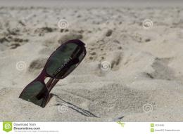 of a pair of sunglasses on the sand of the beach in sunny day 1699