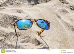 Sunglasses on beach sand which reflects the sun and umbrellas 151