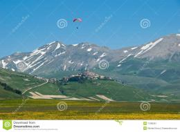 village and meadow in the Piano Grande, Italy with paraglider above 210