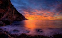 Peaceful ocean and the cloudy sunset sky by the rocky shore wallpaper 1635