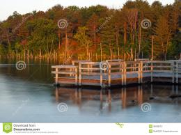 Morning sunrise shines over pier illuminating autumn colors on trees 1135