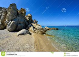 Sandy beach and rocks of unusual shape in morning sunlight under clear 1343