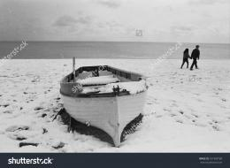 snow covered beach with a boat, and a couple walking past holding 319