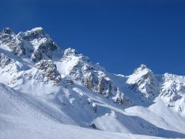 Snow covered rugged mountain peaks in France under a clear crisp blue 1495