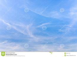 Hazy blue summer sky background with wisps of fine cirrus clouds in an 459