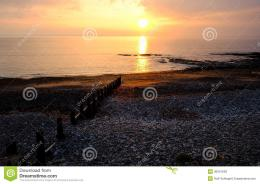 Sunset Over The OceanWood Wave Breakers Leading To The Sun Stock 1250