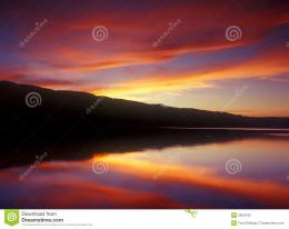 colorful sky at sunset reflecting in a perfectly calm lake 536