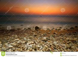 Scenic view of orange sunset with rocky beach in foreground 1062