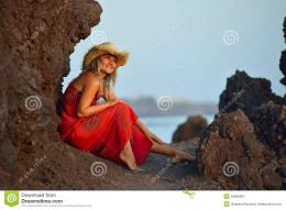 Stock Photo: Young beautiful woman between black rocks on the beach 397