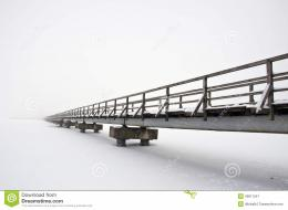 Old long wooden bridge on winter lake snowy ice and early morning fog 733