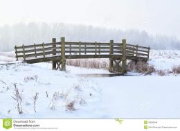Wooden bridge over frozen river in winter 1979