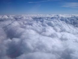 View from an aircraft above a dense layer of white fluffy clouds to 1085