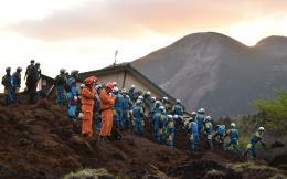 Japanese policemen search for survivors at a landslide site after 973